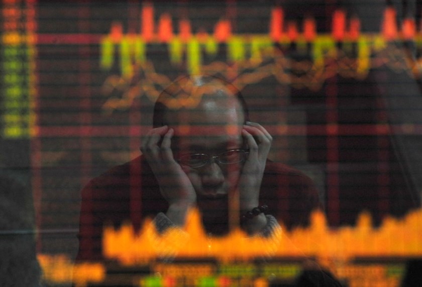 An investor is reflected in a screen showing stock information at a brokerage house in Hefei, Anhui province. Reuters