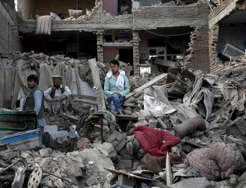 Men sit amid debris of their properties at the site a truck bomb blast in Kabul, August 7, 2015.