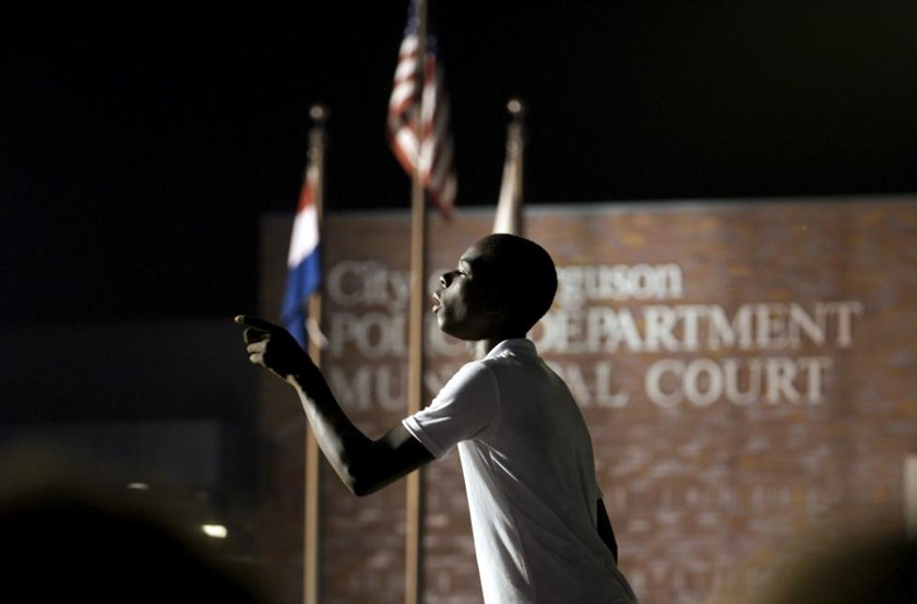 A protester yells at police stationed outside the police department in Ferguson, Missouri August 8, 2015.