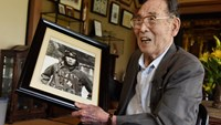 Former Japanese fighter pilot Kaname Harada, 98, holds his portrait taken when he was young as he tells his experience during World War II at his home in Nagano, Nagano Prefecture