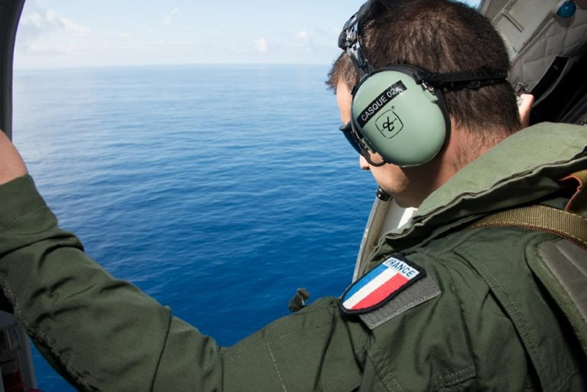 This picture taken by the ECPAD on August 9, 2015 shows a French serviceman looking out over the Indian Ocean, off the French overseas island of La Reunion, during searches for more wreckage of flight MH370