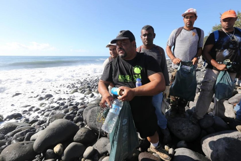 Gerard Agathe (left), president of a platform for 'green' jobs, shows objects found during a search for debris from the ill-fated Malaysia Airlines flight MH370 on a beach in Sainte-Marie de la Reunion on August 10, 2015