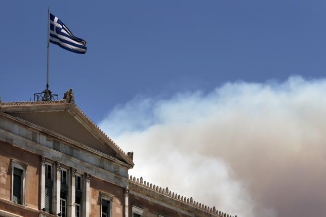 A Greek national flag flutters atop the parliament building as smoke from a raging wildfire rises in Athens, Greece July 17, 2015.