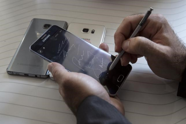 A man writes on a Samsung Galaxy Note 5 at the product's launch event in New York August 13, 2015.