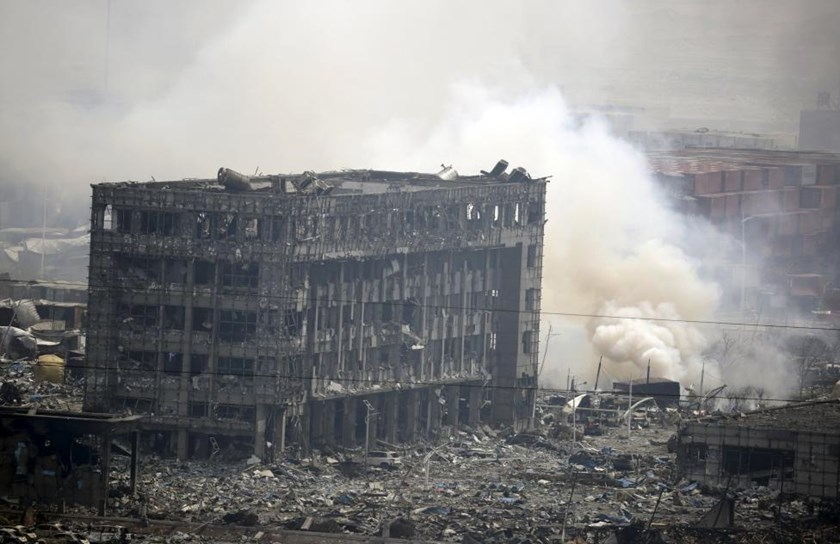 Smoke rises next to a damaged building at the site of the explosions at the Binhai new district in Tianjin, China, August 14, 2015.