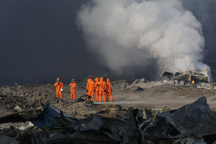 Firefighters inspect the explosion site in Tianjin, China, on Aug. 13, 2015. Photographer: Xinhua News Agency/Getty Images