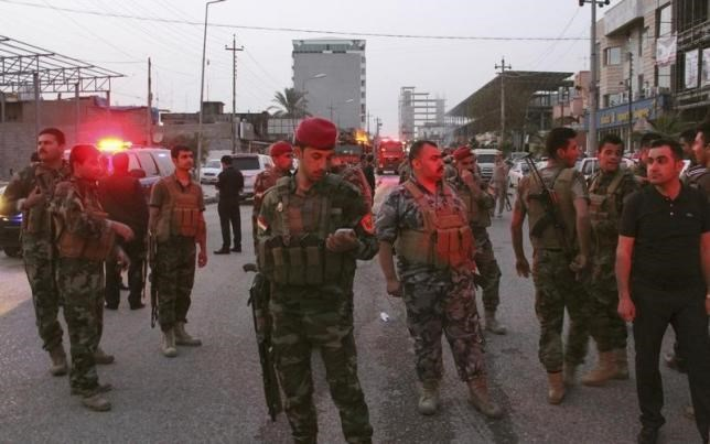 Kurdish security forces gather at the site of a bomb attack in Erbil, the capital of Iraq's Kurdistan region, April 17, 2015.