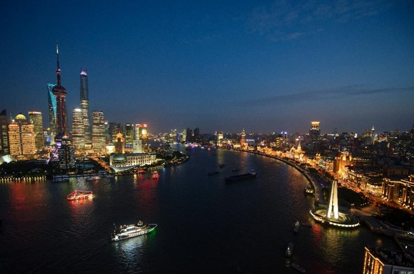 Boats pass by the skyline of the Lujiazui Financial District in Pudong, Shanghai, as seen on August 14, 2015