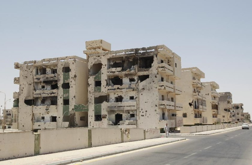 A Libyan man walks past a damaged building in Sirte