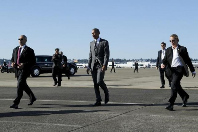 Secret Service agents flank U.S. President Barack Obama as he crosses the tarmac to greet people who watched him arrive aboard Air Force One at the Oregon Air National Guard Base in Portland, Oregon May 7, 2015.