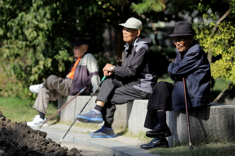 Elderly men sit on benches at Tapgol Park in Seoul, South Korea.