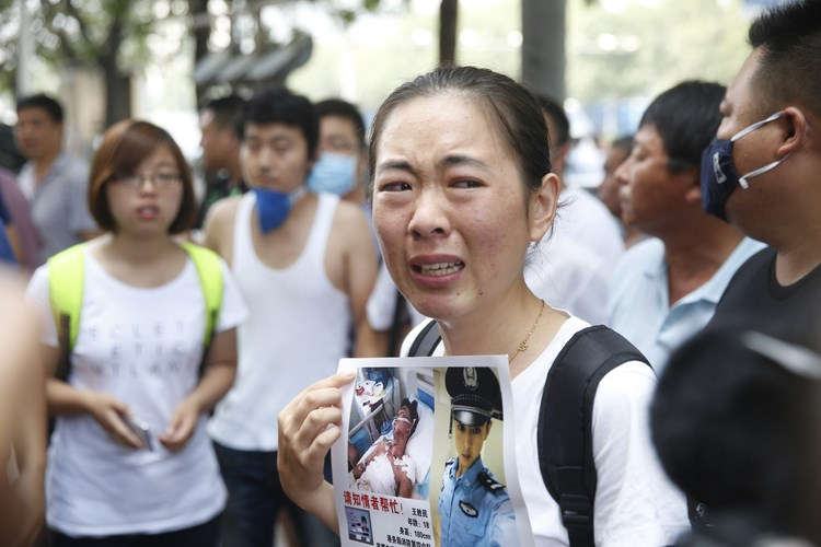 A relative of a missing firefighter protests outside a hotel where authorities are holding a press conference in Tianjin on Sunday. Photographer: AFP/Getty Images