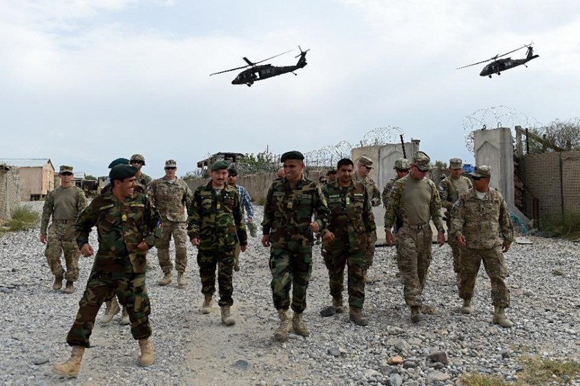 US army and Afghan National Army (ANA) soldiers walk as a NATO helicopter flies overhead at coalition force Forward Operating Base (FOB) Connelly in the Khogyani district in the eastern province of Nangarhar on August 13, 2015