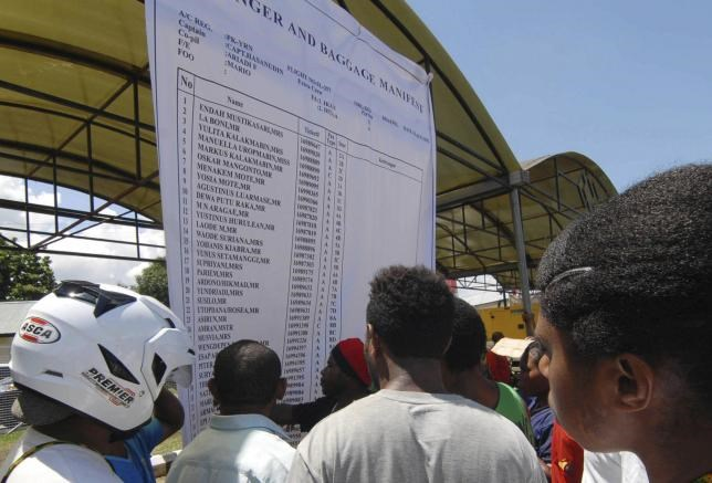 People look at a passenger and baggage manifest of the crashed Trigana Air Service flight at the airport in Sentani, near Jayapura, Papua province, Indonesia, August 17, 2015, in this photo taken by Antara Foto.
