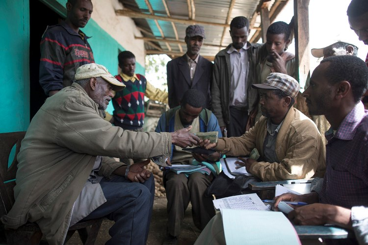 A farmer, left, accepts cash payment for his barley grain in Ethiopian birr banknotes from a buyer for Diageo Plc's Meta Abo brewery in the village of Damo Dulele, Ethiopia, on Feb. 26, 2015.