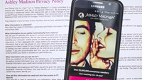 A photo illustration shows the privacy policy of the Ashley Madison website seen behind a smartphone running the Ashley Madison app in Toronto, August 20, 2015.