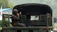 A South Korean soldier talks on a radio as he sits on a military vehicle at the demilitarized zone separating the two Koreas in Yeoncheon, South Korea, August 20, 2015.
