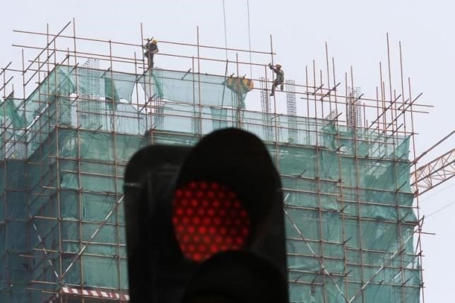 Construction workers are seen behind a traffic signal, at a site for a new business building, in Beijing in this July 12, 2013 file photo.