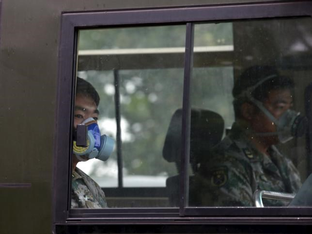 Paramilitary policemen wearing masks ride a vehicle as they travel within a 3-km (2-mile) exclusion zone from last week's explosion site in Binhai new district in Tianjin, China, August 18, 2015.