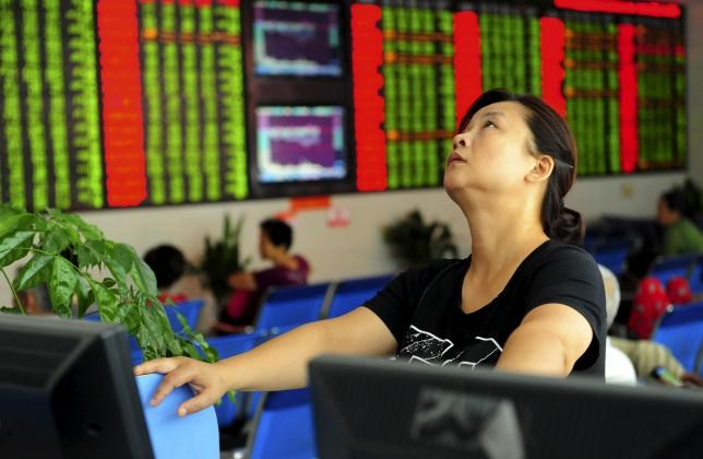 An investor looks up in front of an electronic board showing stock information at a brokerage house in Fuyang, Anhui province, China August 21, 2015.