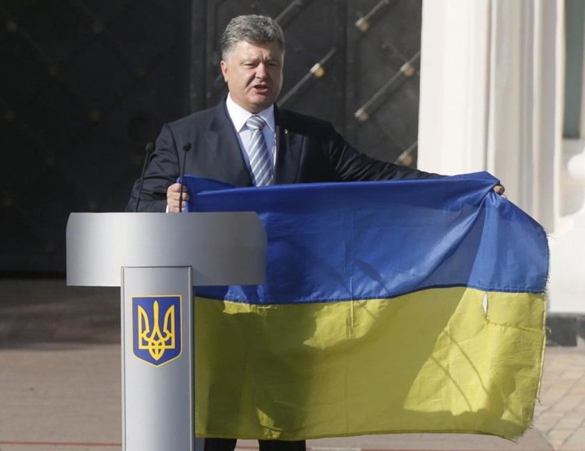 Ukraine's President Petro Poroshenko delivers a speech, while holding a flag brought from eastern regions of the country where a military conflict takes place, during a ceremony marking the Day of the State Flag, on the eve of the Independence Day, in Kiev, Ukraine.