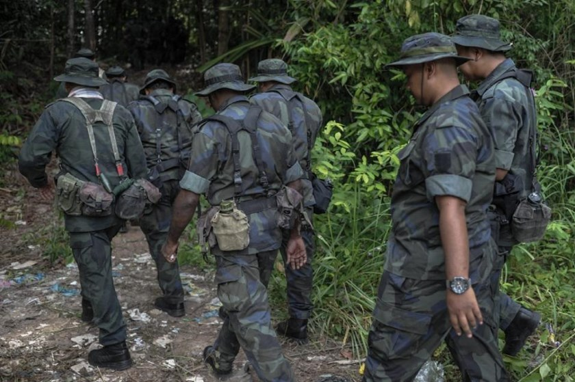 Royal Malaysian Police personnel walk towards a dense jungle area that leads to an abandoned migrant camp, in the northern state of Perlis, in May 2015