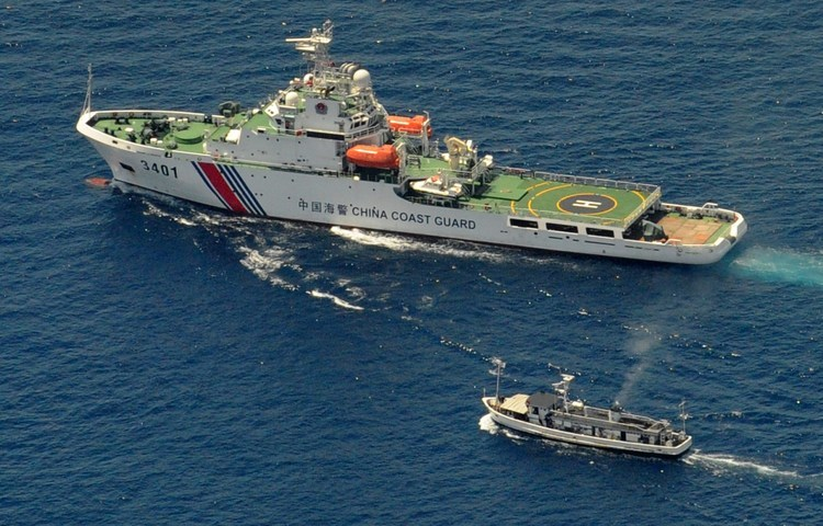 A China Coast Guard ship (top) blocks a Philippine boat from reaching a reef in South China Sea claimed by both countries in 2014.