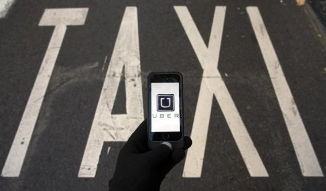 The logo of car-sharing service app Uber on a smartphone over a reserved lane for taxis in a street is seen in this photo illustration taken in Madrid on December 10, 2014.