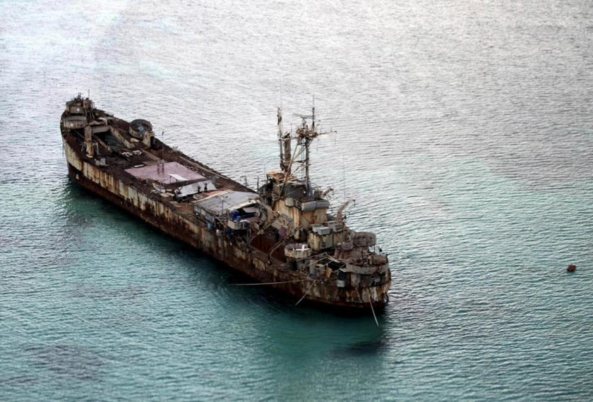 Filipino soldiers wave from the dilapidated Sierra Madre ship of the Philippine Navy as it is anchored near Ayungin shoal (Second Thomas Shoal) in the Spratly group of islands in the South China Sea, west of Palawan, Philippines, May 11, 2015.