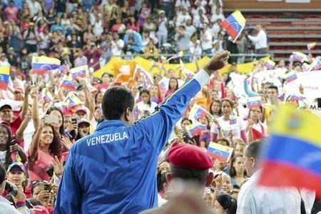 Venezuela's President Nicolas Maduro (C) waves a national flag during a meeting with the National Union of Women (UNAMUJER) in Caracas, in this handout picture provided by Miraflores Palace on August 27, 2015.