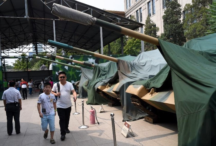 Visitors walk by old army tanks parked outside the Chinese Military museum in Beijing, on August 29, 2015