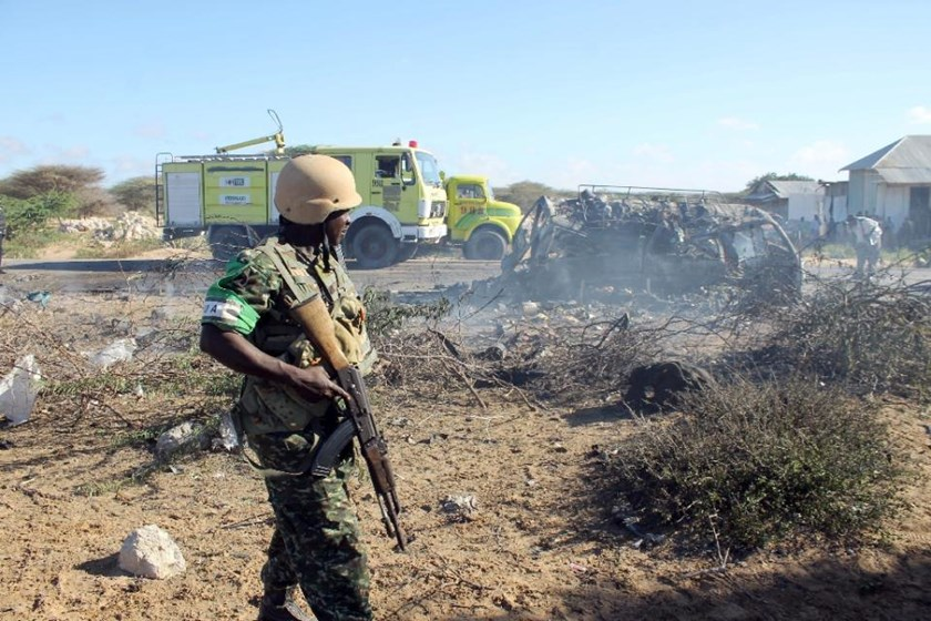 An African Union Mission in Somalia (AMISOM) soldier stands guard close to destroyed vehicles following a suicide attack which targeted a convoy of African Union troops on September 8, 2014