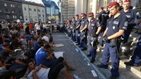 Migrants form a sit-down demonstration as police block the entrance to the main Eastern Railway station in Budapest, Hungary, September 1, 2015.
