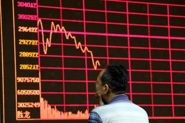An investor looks at an electronic board showing stock information of Shanghai Stock Exchange Composite Index at a brokerage house in Beijing, August 26, 2015.