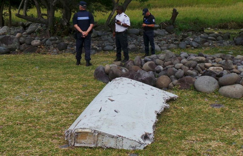 French gendarmes and police stand near a large piece of plane debris which was found on the beach in Saint-Andre, on the French Indian Ocean island of La Reunion, July 29, 2015