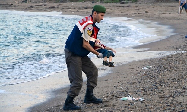 A Turkish police officer carries a young boy who drowned in a failed attempt to sail to the Greek island of Kos. Photo: Reuters