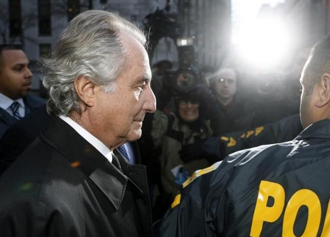 Disgraced financier Bernard Madoff is escorted by police and photographed by the media as he departs U.S. Federal Court after a hearing in New York, January 5, 2009.