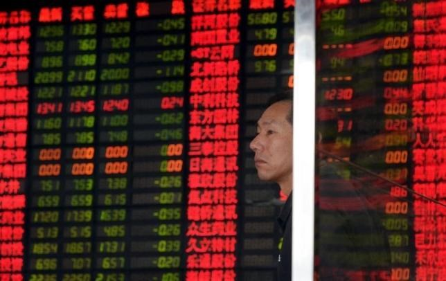 An investor stands in front of an electronic board showing stock information at a brokerage house in Shanghai, China, September 2, 2015.