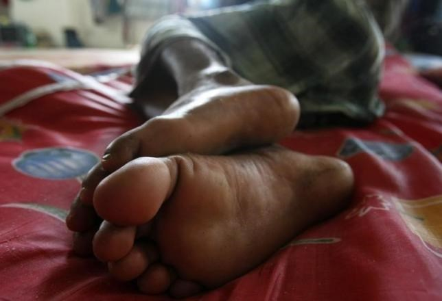 A migrant worker from Bangladesh sleeps on a makeshift bed in a temporary dormitory in Seri Alam near Johor Bahru March 20, 2009.