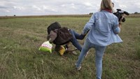 A migrant carrying a child falls after being tripped by TV camerawoman (R) Petra Laszlo while trying to escape from a collection point in Roszke village, Hungary, September 8, 2015.