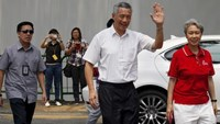 Singapore's Prime Minister and Secretary-General of the People's Action Party Lee Hsien Loong (2nd R) and his wife Ho Ching (R) arrive to cast their votes at a polling center in Singapore September 11, 2015.
