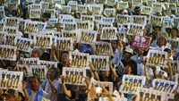 People hold placards denouncing Japan's Prime Minister Shinzo Abe's security-related legislation during an anti-government rally in Tokyo July 24, 2015.