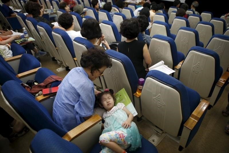 A girl takes a nap next to her grandmother during a child care class for grandparents in Seoul, South Korea, September 1, 2015.