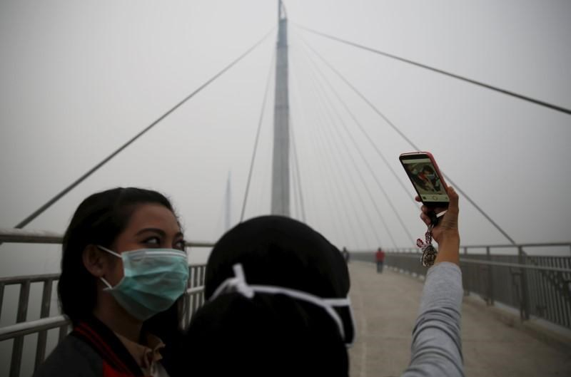 Girls take a selfie at the haze shrouded Batanghari River bridge in Jambi, Indonesia Sumatra island, September 14, 2015.