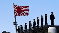 Sailors stand on the deck of the Izumo warship as it departs from the harbor of the Japan United Marine shipyard in Yokohama, south of Tokyo. March 25, 2015.