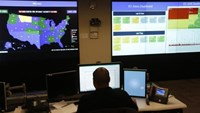 A U.S. Department of Homeland Security employee works in front of a U.S. threat level map and monitoring display inside the National Cybersecurity and Communications Integration Center during a guided media tour in Arlington, Virginia June 26, 2014.