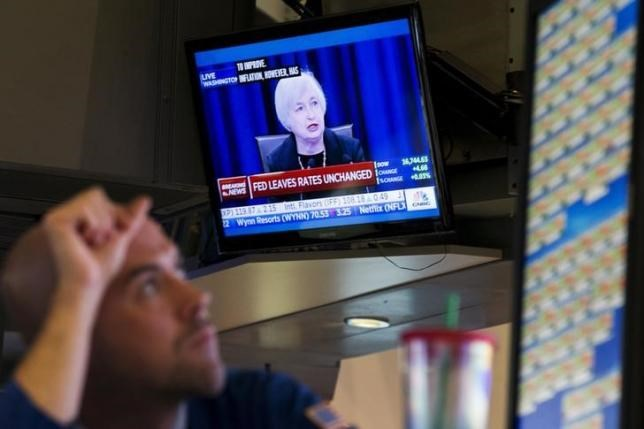 A trader works underneath a television screen showing Federal Reserve Chair Janet Yellen announcing that the Federal Reserve will leave interest rates unchanged on the floor of the New York Stock Exchange in New York September 17, 2015.