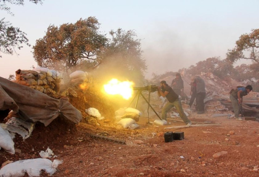 A rebel fighter fires a heavy machine gun during clashes with government forces and pro-regime shabiha militiamen on the outskirts of Syria's northwestern Idlib province on September 18, 2015