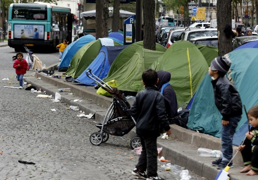 Children play in the street beside tents at unofficial temporary encampment of Syrian refugees and migrants in the Porte de Saint-Ouen district of Paris on September 19, 2015