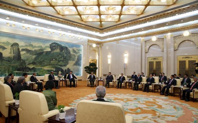 China's President Xi Jinping (front row 8th R) meets with the guests at the Asian Infrastructure Investment Bank launch ceremony at the Great Hall of the People in Beijing in this October 24, 2014 file photo.